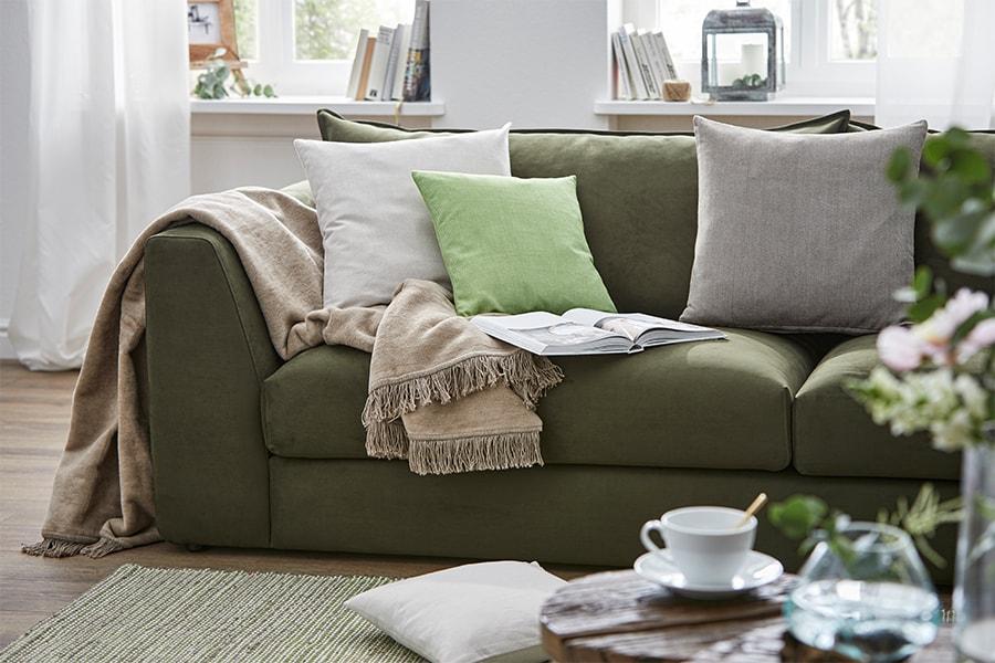 grünes Sofa mit Decke und Kissen